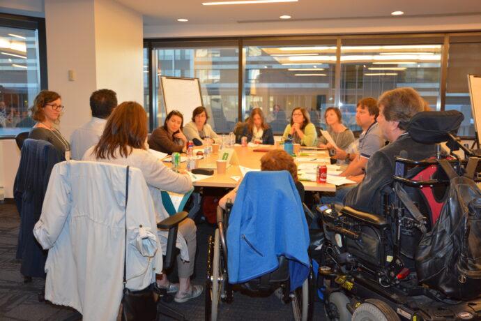 Un groupe de personnes assises autour d'une table discutent