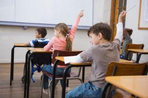 Des enfants assis dans une salle de classe lèvent la main pour répondre à une question