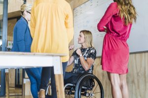 A photo of disabled businesswoman with coworkers at workplace. Smiling female is sitting on wheelchair with colleagues at table. They are in creative office.