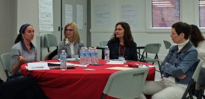 Trois personnes assises à une table écoutant une collègue présentant son sujet de projet.