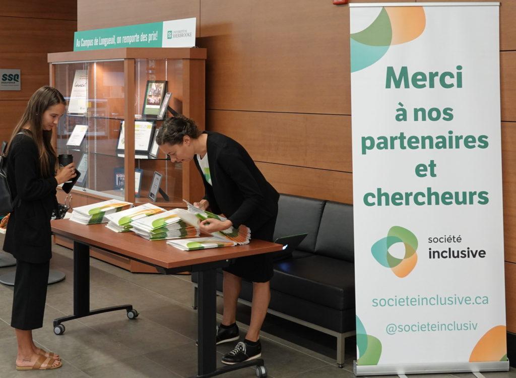 Fabienne à l'accueil. Sur l'affiche aux couleurs de Société inclusive (orange, bleu et vert), on peut lire «Merci à nos partenaires et chercheurs».