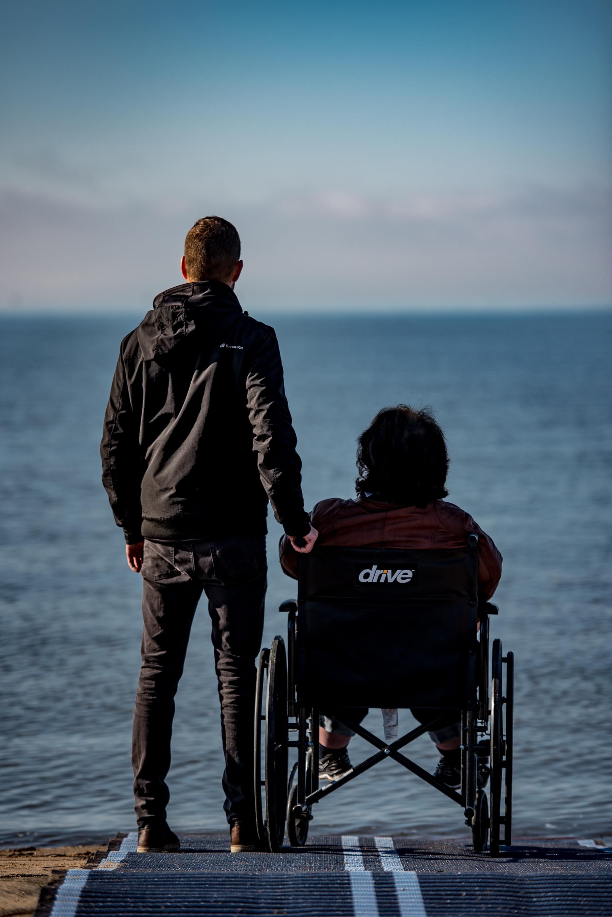 Un homme, sur une plage, se tient debout à côté d'une femme en fauteuil roulant, une main tenant la poignée du fauteuil. Tous font face à une étendue d'eau.